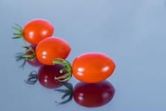 Três vermelho Cherry Tomatoes Lining acima no espelho Foto de Stock Royalty Free