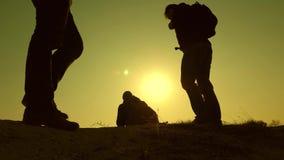 Três viajantes descem de um monte nos raios do sol um depois que outro vão além do horizonte Trabalhos de equipa dos executivos video estoque