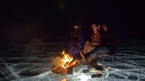 Três viajantes pelo gelo do fogo exatamente na noite Acampamento no gelo A barraca está ao lado do fogo Lago Baikal Próximo há video estoque
