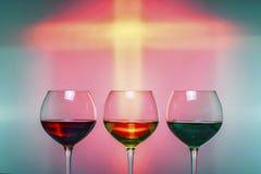 Três vidros com bebidas coloridas em um fundo festivo colorido Imagens de Stock