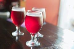 Três vidros com vinho tinto em uma tabela de madeira Os vidros da cerveja da cereja estão na tabela Há ninguém no quadro imagem de stock