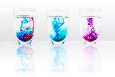 Três vidros da água e da tinta colorida Fotografia de Stock Royalty Free
