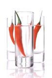 Três vidros da vodca com pimenta de pimentão vermelho imagens de stock royalty free