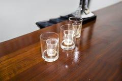 Três vidros de tiro vazios em uma barra Imagens de Stock