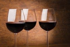Três vidros de vinho meio cheios Fotografia de Stock