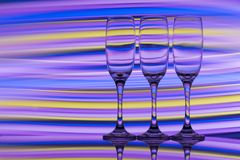 Três vidros do champanhe em seguido com um arco-íris da pintura clara colorida atrás deles imagem de stock