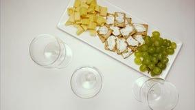 Três vidros do vinho, vermelho, cor-de-rosa e branco, na tabela com um prato do petisco Pare o movimento, animação vídeos de arquivo