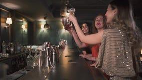 Três vidros felizes do tim-tim das mulheres que sentam-se no fim do contador da barra acima As meninas têm a celebração junto As  video estoque