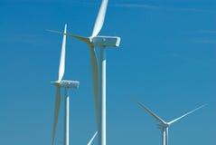 Três windturbines no céu azul Imagem de Stock Royalty Free