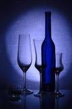 Três wineglasses, um castiçal e um frasco foto de stock