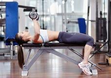 Tríceps y pecho de trabajo de la mujer con pesas de gimnasia fotografía de archivo