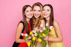 Trío bonito, agradable de muchachas en vestidos, teniendo tulipanes coloridos adentro Imagenes de archivo