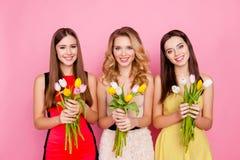 Trío bonito, agradable de muchachas en vestidos, teniendo tulipanes coloridos adentro Fotografía de archivo libre de regalías