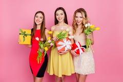 Trío bonito, agradable de muchachas en vestidos, teniendo tulipanes coloridos adentro Imagen de archivo