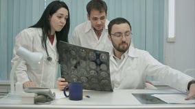 Trío de los médicos asustados jovenes que comprueban al paciente almacen de metraje de vídeo