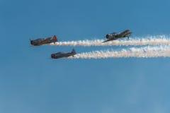 Trío del Texan AT-6 con humo y el cielo azul Imagenes de archivo