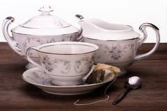 Trío del tiempo del té del cuenco de la taza de té, de la desnatadora y de azúcar imagen de archivo libre de regalías