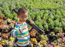 Trípodes que llevan del muchacho asiático que se colocan en jardín de flores Fotos de archivo libres de regalías