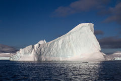 Trójgraniasta góra lodowa w Antarktycznym nawadnia letniego dzień Zdjęcie Royalty Free