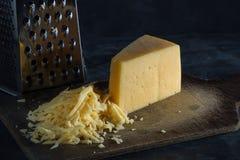 Trójgraniasty kawałek ser i kraciasty ser na desce zdjęcia royalty free