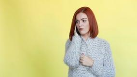 Tröja för slags tvåsittssoffa för känslomässigt röd haired kvinna som bärande grå talar på appelltelefonen stock video