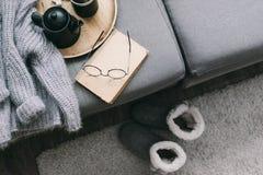 Tröja och läsning på soffan Arkivbilder