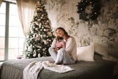 tröjan och flåsanden för Mörker-haired flicka rymmer den iklädda vita en gåva för nytt år i hennes händer som sitter på sängen me arkivbild