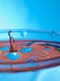 Tröpfchen, das in das blaue Wasser fällt stockbild