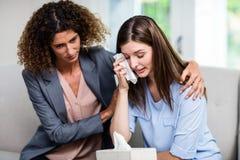 Tröstende deprimierte Frau des weiblichen Psychologen auf Sofa zu Hause Lizenzfreies Stockfoto