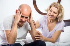 Tröstender Sorgen machender Mann der reifen Freundin, der auseinander sitzt stockbild