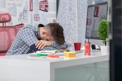 Trött överansträngd affärsman som sover över ett skrivbord på jobbet i hans kontor arkivbilder