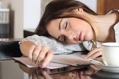 Trött överansträngd kvinna som vilar, medan skriva anmärkningar arkivfoton