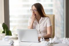 Trött överansträngd sömnig affärskvinna som gäspar på arbetsplatsen, arbete arkivbild