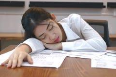 Trött överansträngd ung asiatisk affärskvinna som ner i regeringsställning ligger på skrivbordet royaltyfri fotografi
