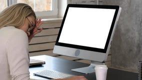 Trött affärskvinna på hennes skrivbord framme av bildskärmen Vit skärm arkivbild