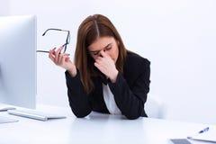 Trött affärskvinna som gnider henne ögon royaltyfri foto