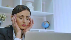 Trött affärskvinna som har en huvudvärk, medan arbeta på hennes bärbar dator i ljust kontor stock video