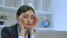 Trött affärskvinna som har en huvudvärk, medan arbeta på hennes bärbar dator i ljust kontor lager videofilmer
