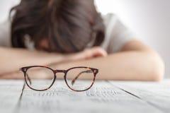 Trött affärskvinna som sovande faller på hennes arbetsplats med ögongl royaltyfri foto