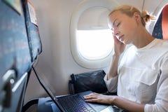 Trött affärskvinna som ta sig en tupplur på flygplanet under hennes affärstur som wokar uppgifter royaltyfria bilder