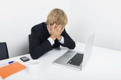 Trött affärsman med händer på framsidasammanträde på skrivbordet vid bärbara datorn Royaltyfri Bild