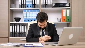 Trött affärsman på hans skrivbord som spelar imaginära valsar stock video