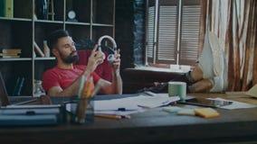 Trött affärsman som sätter fot på tabellen och lyssnande musik i hörlurar stock video
