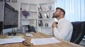 Trött affärsman som sent arbetar på natten och lossar hans band i kontoret arkivfilmer