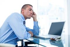 Trött affärsman som ser hans bärbar dator Arkivfoton