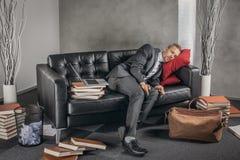 Trött affärsman som sover på soffan Royaltyfri Foto