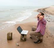 Trött affärsmansammanträde med anteckningsboken på stranden Royaltyfria Bilder