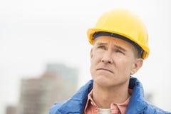 Trött arbetare som bort ser på konstruktionsplatsen royaltyfria bilder