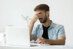 Trött arbetare som masserar ögon som lider från huvudvärk Arkivbilder