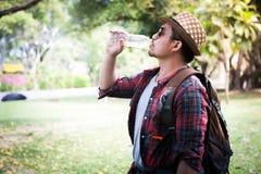 Trött asiatisk man med ryggsäckdricksvatten royaltyfri bild